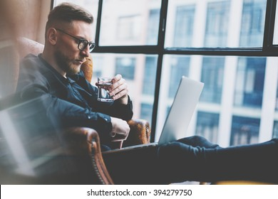 Bearded young businessman working on modern loft office. Man sitting in vintage chair, holding glass water. Using contemporary notebook, panoramic windows background. Horizontal, film effect.
