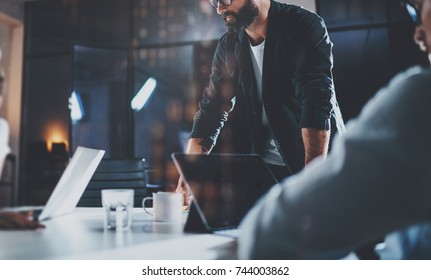 Bearded young coworker working at night office with partners.People using contemporary laptop and modern smartphone.Horizontal.Blurred background.Cropped
