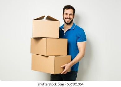 bearded young man in blue shirt carrying three carton boxes on a white wall