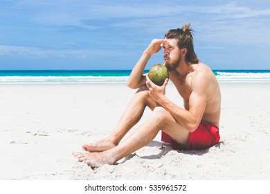 Bearded young man enjoying coconut on tropical beach while summer vacation