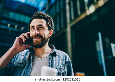 Bearded young man laughing while calling on smartphone device strolling in urban setting of modern city.Positive hipster guy communicating on mobile phone walking on street of business center