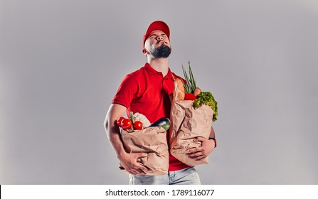 Bearded young man in red T-shirt and cap holding two large heavy bags with food isolated on gray background. Fast food delivery to your home.