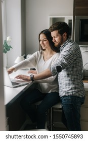 Bearded young man shows his work to a girl on a laptop screen next to a window in the kitchen. Guy drinking coffee and using notebook. Daily life of a male and female in apartment.