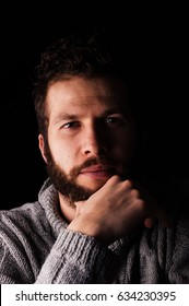 A bearded young man in a sweater stroking his beard looks at the camera on a dark background. The concept of calm and modern men or hipster.