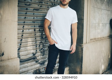 Bearded young man wearing white blank t-shirt and blue jeans, standing on the street