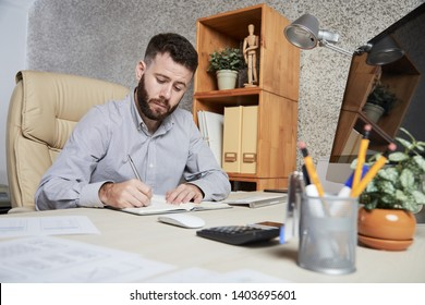 Bearded young manager sitting at office desk and writing new plans and ideas in his notepad