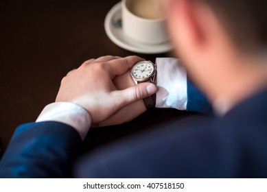 Bearded young successful businessman punctual keeps track of time, a man in a suit waits for the client
