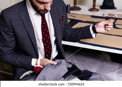 Bearded young tailor wrapped up in sewing male jacket with needle and thread while sitting at working table, interior of atelier on background