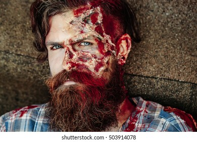 Bearded zombie man with beard halloween vampire or bloody war soldier with wounds and red blood outdoors on asphalt road