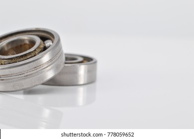 Bearing used and dirty lubricant on white background. Selective focus.