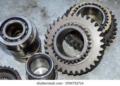 The bearings and gears of the car's manual transmission lie on a metal worktable in the auto repair shop