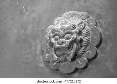 beast sculpture on red wooden door in a temple, closeup of photo