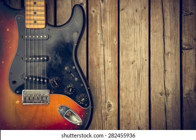 Un corps de guitare électrique vintage défoncé et sale sur fond naturel de planches à grains de bois.