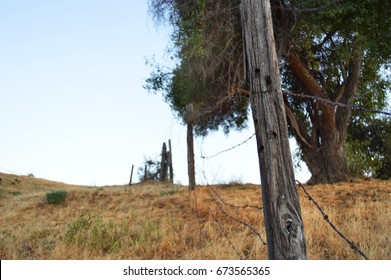 A beat up fence along a dry hill in Yucaipa, California.