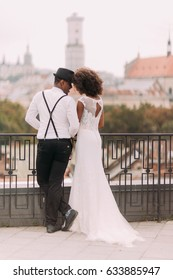 Beatiful african newlyweds holding each other on the terrace with amazing Lviv architecture background