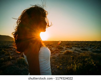 Beatiful carefree young woman with wind in her hair at beach sunset. Hipster girl with hairstyle enjoy summer sunset fun. Happy people traveling lifestyle concept.