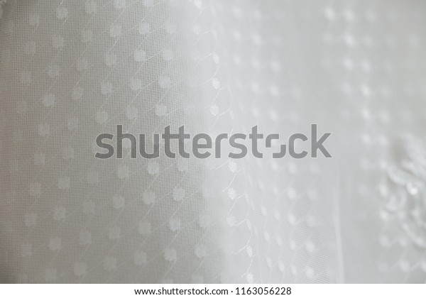 Beatiful and delicate white lace fabric detail from a bridal wedding gown. Unique pattern.
