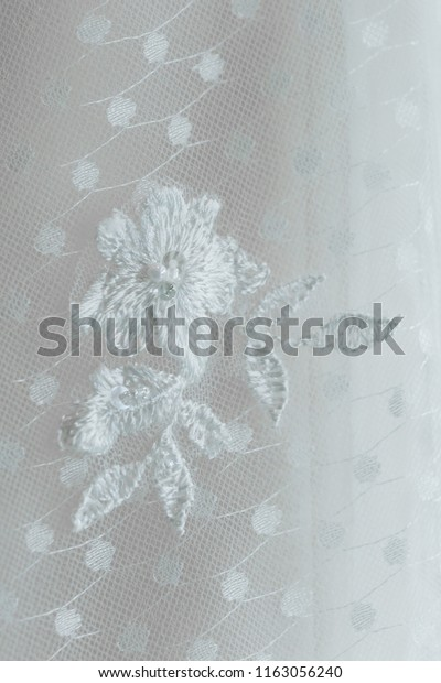 Beatiful and delicate white lace fabric detail from a bridal wedding gown.