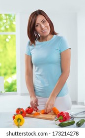 beatiful female cutting vegetables on table