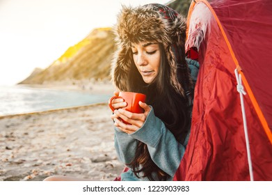 Beatiful female hiker drinking coffee from the cup at morning sitting in the tent. Concept about hiking, people, sport and lifestyle