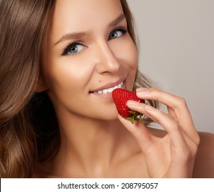 Beatiful girl with Perfect smile eat red strawberry. white teeth and healthy food