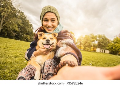 Beatiful and happy caucasian girl taking a selfie with her dog at the park on vacation. Concept about animals, technology, people and lifestyle