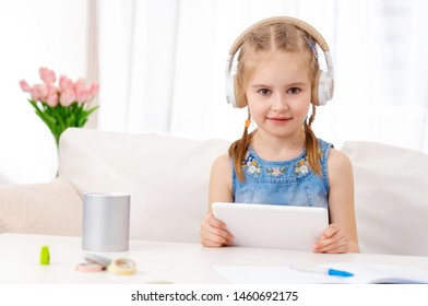 Beatiful little girl with white tablet with headphones on, in the room