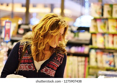 beatiful matured woman looking for christmas gifts in bookstore