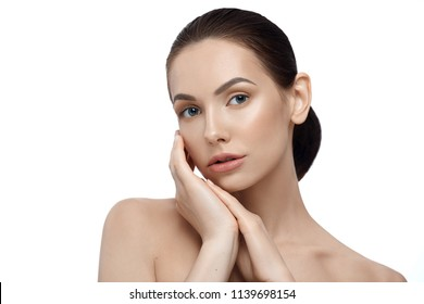 Beatiful model posing with naked shoulders looking at camera with big blue eyes. Touching face tenderly. Having plump lips, brown hair, perfect shape of eyebrows. Standing on white studio background.