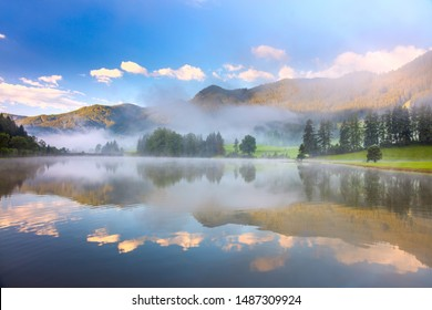 Beatiful morning landscape in Alps mountain and lake with reflections, foggy