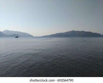 Beatiful sea summer panorama.  Beach scene at Pukka region, yachts, boats, mountains, shot at Marmaris, Turkey. blue sky, tourists in swimsuits, umbrellas, people resting, swimming