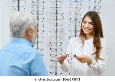 Beatiful smiling assistant showing eyeglasses to old man. Advising which optical glasses are better. Tranparent stand with glasses set in front of white wall on background. friendly and kind.