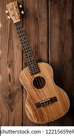 beatiful tenor ukulele made of zebrawood on aged dark wood background