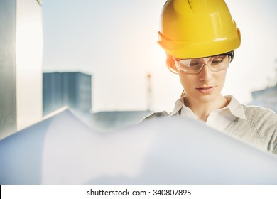 beatiful woman engineer is reviewing the plans of a construction work
