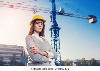 beatiful woman engineer is standing serious in front of a crane