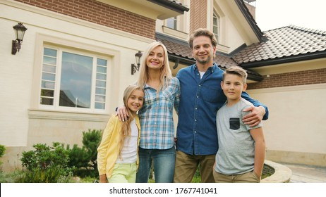 Beatiful young family possing and smiling on camera on the new house background.