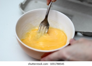 Beating egg with fork. Making omelette series.