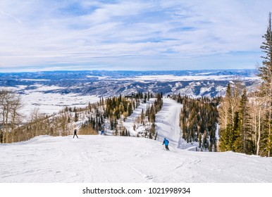 Beatutiful view of a Colorado ski slope; people skiing down, someone takes pictures; mountains and blue sky in the background