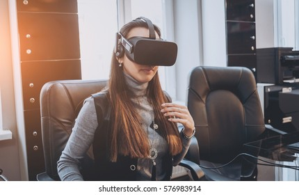 The beatyfull girl wearing virtual reality goggles at the office