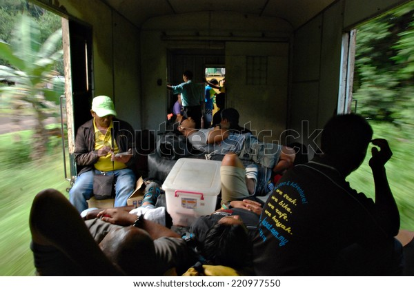 Beaufort, Sabah, Malaysia : February 13, 2014. A group of unidentified train passengers taking a rest in one of the coaches of Sabah State Train moving pass vegetation along Beaufort - Tenom route.