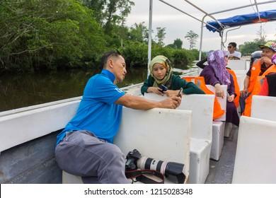 Beaufort, Sabah, Malaysia-September 16, 2018 : Tour guild explain something to tourist at WILDLIFE SAFARI RIVER CRUISE at Kota Klias, Beaufort, Sabah Borneo for see the beautiful nature rainforest