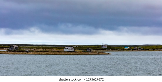 Beaufort sea arctic ocean coast dotted with shacks and small cabins on shore near Inuvialuit town of Tuktoyaktuk, Northwest Territories, NWT, Canada
