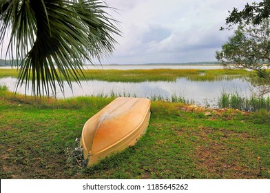 BEAUFORT, SOUTH CAROLINA - October 8, 2008: An overturned boat lies beneath a Palmetto tree along the banks of a marsh inlet as stormy weather approaches from the Atlantic.