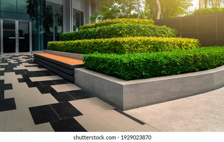 Beauiful outdoors gardening decoration with bench of an modern office building, outdoor gardening image for corporate buildings concept.