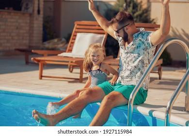 Schöner, fröhlicher Vater und Tochter, die am Rande eines Swimmingpools sitzen und sich an einem heißen Sommertag im Freien amüsieren