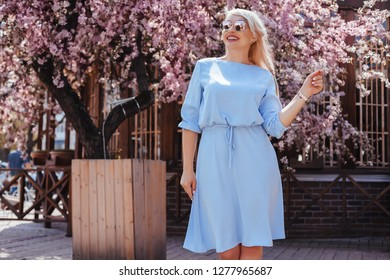 Beauitful plus size model wearing blue dress and trendy sunglasses enjoying smell of pink blooming spring tree outdoor on the city street.