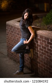 Beauitiful young girl, wearing ripped jeans is posing, while leaning against stone wall