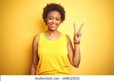 Beauitul african american woman wearing summer t-shirt over isolated yellow background showing and pointing up with fingers number two while smiling confident and happy.