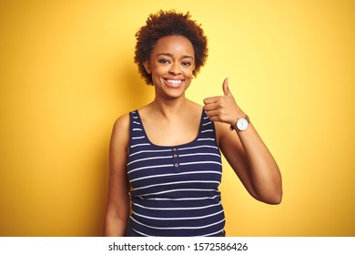 Beauitul african american woman wearing summer t-shirt over isolated yellow background doing happy thumbs up gesture with hand. Approving expression looking at the camera showing success.
