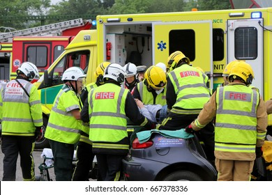 Beaulieu, Hampshire, UK - May 29 2017: Firemen and paramedics removing the casualty from a car with a spineboard during a vehicle rescue demonstration by the UK Fire Brigade